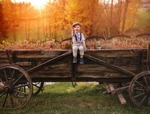 Porträt eines netten kleinen Jungen, der auf einem Wagen sitzt stockbilder