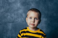 Porträt eines netten kleinen Kindes des Umkippens, das Kamera gegen Betonmauerhintergrund betrachtet stockfotografie