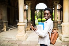 Porträt eines netten lächelnden afrikanischen Studentenmädchens mit den Daumen herauf tragende Rucksack- und Bücher am Universitä stockfotos