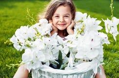 Porträt eines netten lächelnden Kindes mit einem Blumenkorb stockfotografie
