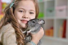 Porträt eines netten Mädchens, das mit Chinchilla spielt lizenzfreies stockbild