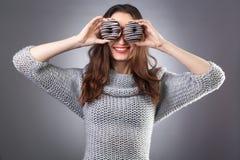 Porträt eines netten Mädchens in der grauen Strickjacke, die mit Schaumgummiringen an ihrem Gesicht auf dem dunklen Hintergrund a lizenzfreie stockfotos