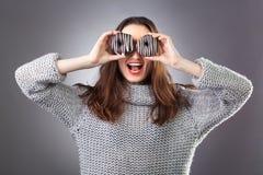 Porträt eines netten Mädchens in der grauen Strickjacke, die mit Schaumgummiringen an ihrem Gesicht auf dem dunklen Hintergrund a lizenzfreies stockfoto