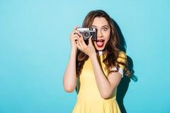 Porträt eines netten Mädchens im Kleid unter Verwendung der Retro- Kamera Lizenzfreie Stockfotos