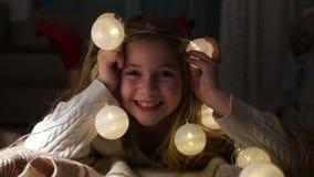 Porträt eines netten Mädchens mit Weihnachtslichtern Kind liegt auf dem Boden und spielt mit der Weihnachtsgirlande, kreativ stock footage