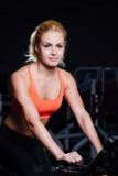 Porträt eines netten netten weiblichen Trainings auf Eignung die Hometrainerdunkelheit an der Turnhalle Stockbilder