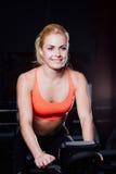 Porträt eines netten netten weiblichen Trainings auf Eignung die Hometrainerdunkelheit an der Turnhalle Stockfotos
