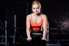 Porträt eines netten netten weiblichen Trainings auf Eignung die Hometrainerdunkelheit an der Turnhalle Stockfoto