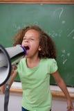 Porträt eines netten Schulmädchens, das durch ein Megaphon schreit Stockbild