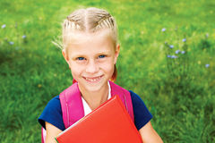 Porträt eines netten Schulmädchens mit einer Schultasche und Lehrbüchern T Stockbilder