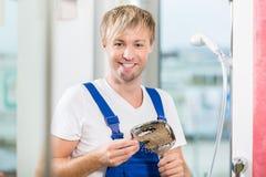 Porträt eines netten Wartungsarbeiters, der einen Hahn hält Stockfotografie
