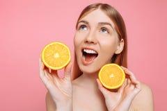 Porträt eines netten weiblichen Mädchens, natürliche klare Haut, Mädchen mit zwei orange Scheiben, lokalisiert auf einem rosa Hin stockbild