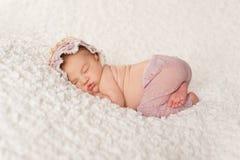 Porträt eines neugeborenen Mädchens mit Spitze-Hosen und Mütze stockfoto
