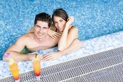 Porträt eines Paares, das ein Cocktail in einem Pool lächelt und trinkt Stockfoto