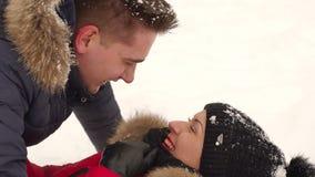 Porträt eines Paares in der Liebe, die auf dem Schnee liegt stock video footage