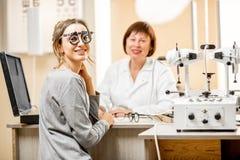 Porträt eines Patienten der jungen Frau mit älterem Augenarzt lizenzfreie stockfotos