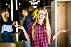 Porträt eines Positivs, welches die junge Frau steht mit ihren offenen Palmen mit den Mitarbeitern sprechen im Hintergrund schaut Stockfotos