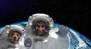 Porträt eines Raumfahrers mit einem Hund auf dem Hintergrund der Kugel stockbild