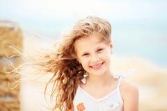Porträt eines recht kleinen Mädchens mit dem Wellenartig bewegen in den Wind langes ha Lizenzfreie Stockbilder