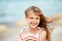 Porträt eines recht kleinen Mädchens mit dem Wellenartig bewegen in den Wind langes ha Stockfotos