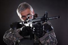 Porträt eines reifen Soldaten Aiming With Gun Lizenzfreies Stockfoto