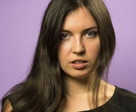 Porträt eines reizend Brunettemädchens auf einem purpurroten Hintergrund Lizenzfreies Stockfoto
