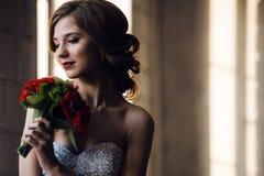 Porträt eines reizend Mädchens mit schönem Lächeln und rotem Lippenstift, oben schauend, mit einem Blumenstrauß von roten Rosen a Stockbilder