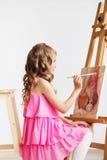 Porträt eines reizenden kleinen Mädchens, das ein Bild in einem Studio malt Lizenzfreie Stockfotografie