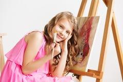 Porträt eines reizenden kleinen Mädchens, das ein Bild in einem Studio malt Lizenzfreies Stockfoto