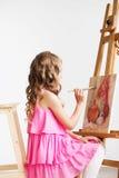 Porträt eines reizenden kleinen Mädchens, das ein Bild in einem Studio malt Lizenzfreie Stockfotos