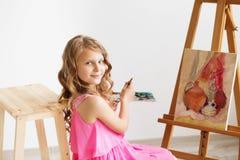 Porträt eines reizenden kleinen Mädchens, das ein Bild in einem Studio malt Stockfotografie