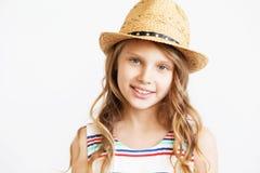 Porträt eines reizenden kleinen Mädchens mit Strohhut gegen ein Weiß lizenzfreie stockbilder