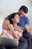 Porträt eines reizenden Paares, das online ihre Feiertage bucht Lizenzfreies Stockbild