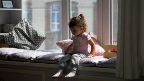 Porträt eines süßen, glücklichen kleinen Mädchens, das auf Fensterbrett sitzt stock video