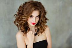 Porträt eines schönen bezaubernden Brunette mit dem gelockten Haar und b lizenzfreie stockfotos