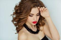 Porträt eines schönen bezaubernden Brunette mit dem gelockten Haar und b lizenzfreies stockbild