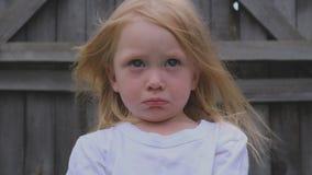 Porträt eines schönen blauäugigen, blonden kleinen Mädchens stock footage