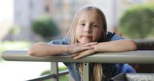 Porträt eines schönen blonden Mädchens auf dem Balkon im Sommer stock footage