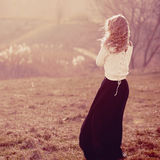 Porträt eines schönen blonden Mädchens in den weißen Pullovern, stehend mit seinem zurück Stockfotografie