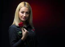 Porträt eines schönen blonden Mädchens mit einer roten Rose in ihrer Hand lokalisiert Stockfoto