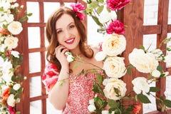 Porträt eines schönen Brunettemädchens in einem Sommerkleid unter einem Blumenbogen lizenzfreie stockfotos