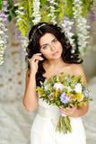 Porträt eines schönen Brunettemädchens in einem weißen Kleid mit einem BO Stockfoto