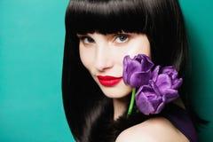 Porträt eines schönen Brunettemädchens mit einer lila Tulpe auf einem blauen Hintergrund Lizenzfreies Stockfoto