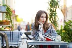 Porträt eines schönen jungen Mädchens, das in einem Café auf dem stre sitzt Lizenzfreie Stockfotos