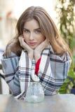 Porträt eines schönen jungen Mädchens, das in einem Café auf dem stre sitzt Lizenzfreie Stockbilder