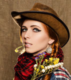 Porträt eines schönen jungen Mädchens in einem Cowboyhut mit wilden Trockenblumen Stockbilder