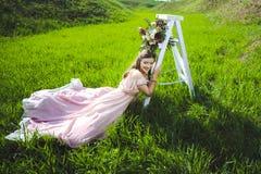Porträt eines schönen jungen Mädchens in einem Fliegenbrautangebot-Rosakleid auf einem Hintergrund des grünen Feldes, lacht sie u Stockbild