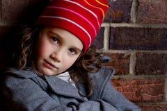 Porträt eines schönen jungen Mädchens im Hut und in Mantel, die auf Backsteinmauer sich lehnen Stockfotos
