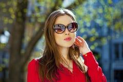 Porträt eines schönen jungen Mädchens im roten Hemd auf dem backgroun Stockbilder