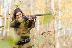 Porträt eines schönen jungen Mädchens im Tarnungsjäger mit Schrotflinte Lizenzfreie Stockfotografie